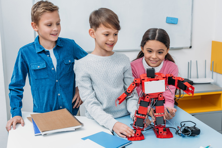 happy schoolchildren touching red handmade robot at desk in stem class Stock Photo