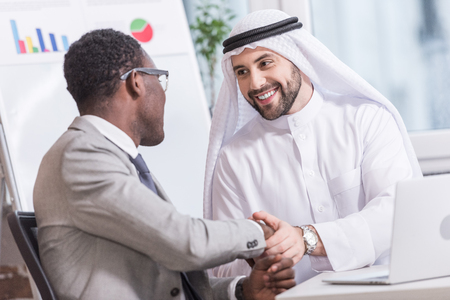 Arabian businessman shaking hands with african american partner in office