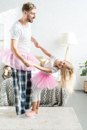 happy father and little daughter in pink tutu skirts holding hands and dancing at home Foto de archivo - 112990153