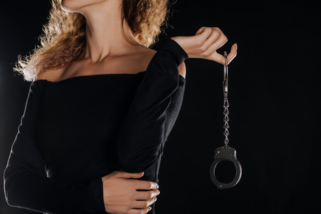 partial view of curly woman holding handcuffs isolated on black Stock Photo - 112990155