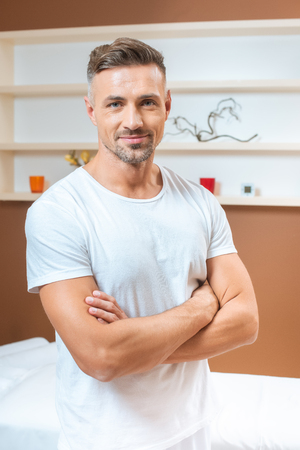 Handsome therapist standing with crossed arms in room