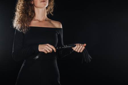 adult woman holding leather flogging whip isolated on black