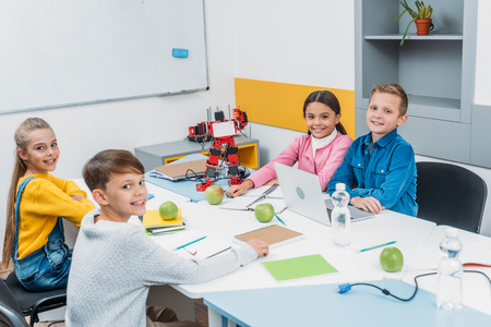 joyful children looking at camera at STEM robotics lesson Фото со стока