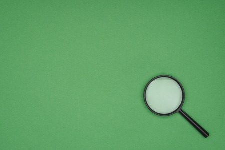 Top view of magnifying glass on green background Stock Photo