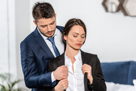 handsome boyfriend helping attractive girlfriend wearing jacket in morning at home