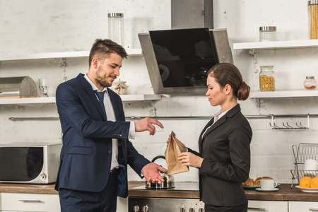 girlfriend giving lunch to boyfriend in morning at kitchen, social roles concept Stock Photo