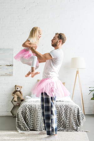 side view of happy father and cute little daughter in pink tutu skirts dancing at home Foto de archivo - 112990213