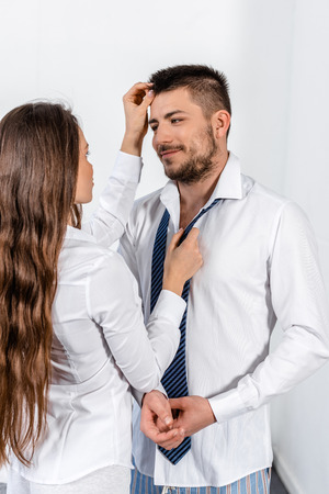girlfriend tying boyfriend tie and touching his hair in morning on weekday in bedroom, social role concept