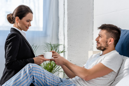 side view of girlfriend in suit giving cup of coffee to boyfriend in pajamas in bedroom in morning, social role concept Stock Photo
