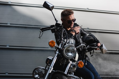 classic rider in black sunglasses sitting on motorcycle in garage Stock Photo