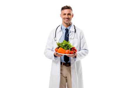 doctor looking at camera and holding plate of fresh vegetables isolated on white, healthy eating concept 写真素材