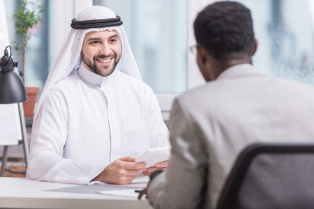 Arabian businessman smiling and holding digital tablet in office