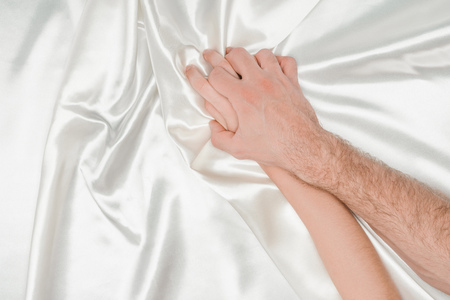 top view of male hand tightly holding female hand on silk white cloth Standard-Bild