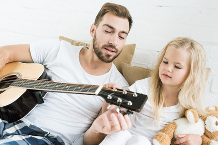 father and cute little daughter playing acoustic guitar together on bed Stock Photo