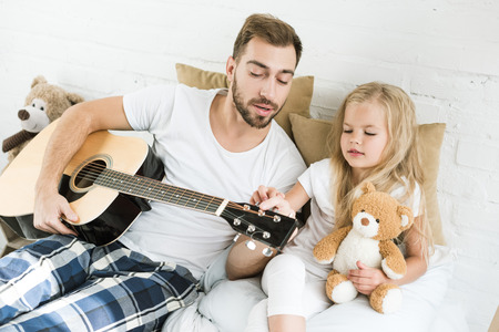 father and cute little daughter with teddy bear looking at acoustic guitar on bed