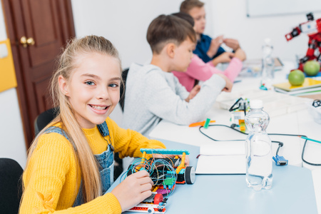 adorable schoolgirl holding robot model, looking at camera while classmates having STEM lesson 写真素材
