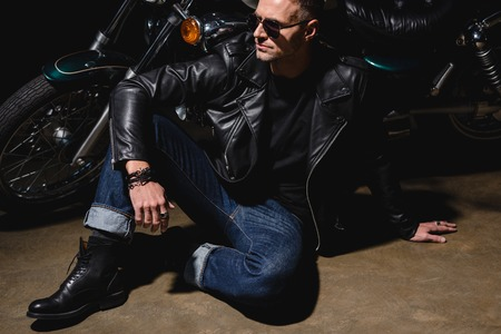 man in black sunglasses sitting by motorcycle in garage Stock Photo