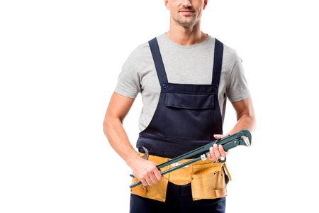 cropped view of worker in overalls holding pipe wrench isolated on white