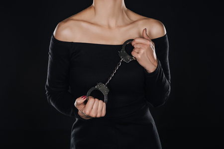 cropped view of woman with open shoulders holding handcuffs isolated on black