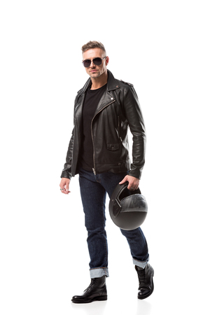 handsome man in leather jacket and sunglasses holding motorcycle helmet isolated on white
