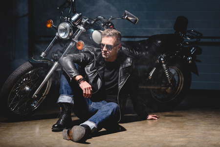 handsome biker in sunglasses sitting on floor next to motorcycle in garage