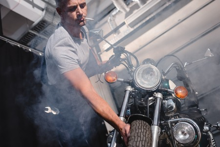 guy smoking cigarette and checking motorbike front wheel in garage Banque d'images - 112990807