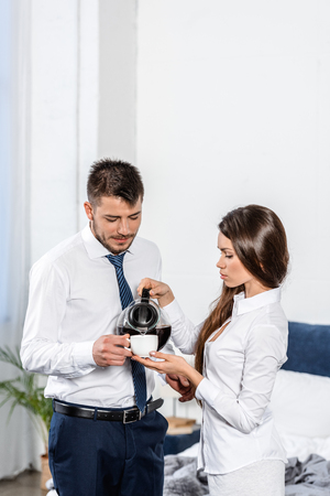 girlfriend pouring coffee into boyfriend cup in morning at home, social role concept Stock Photo
