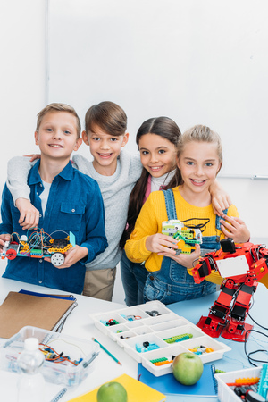 happy schoolchildren looking at camera and holding handmade robots in stem class