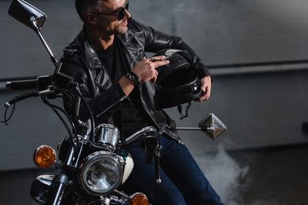 handsome motorbiker in sunglasses standing by motorcycle in garage and smoking cigarette