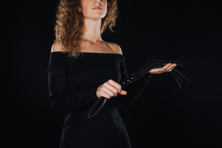 curly adult woman holding flogging whip isolated on black