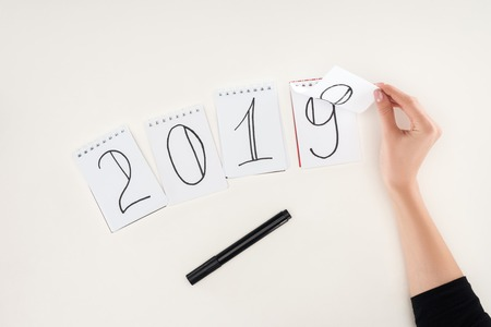 partial view of woman flipping over date written on notes symbolizing change from 2018 to 2019 isolated on white Stock Photo