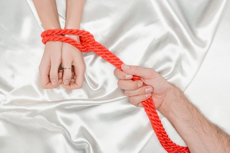 cropped view of male hand bounding female hands with bright red rope