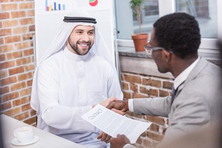Multi-etnische zakenlieden die handen schudden en glimlachen op kantoor Stockfoto