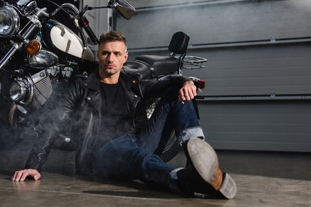 handsome guy sitting on ground by motorcycle in garage Stock Photo