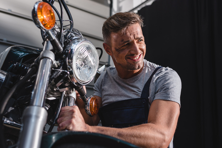 smiling mechanic checking motorcycle front wheel in garage Stock Photo