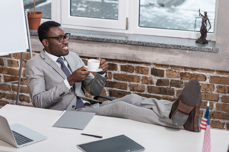 african american businessman with coffee cup putting feet up in office