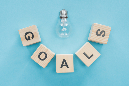 top view of light bulb over goals word made of wooden blocks on blue background, goal setting concept