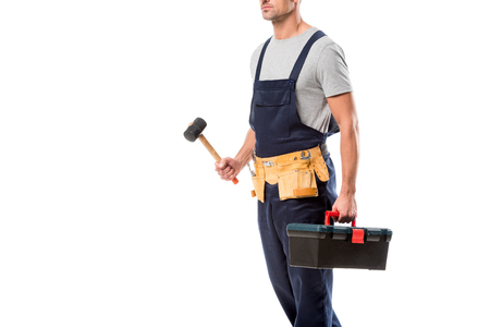cropped view of construction worker holding hammer and tool box isolated on white