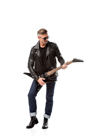 stylish adult man in leather jacket playing electric guitar isolated on white Фото со стока