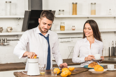 boyfriend making orange juice and girlfriend standing with cup of coffee in kitchen