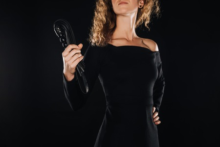 cropped view of curly woman holding leather flogging whip isolated on black