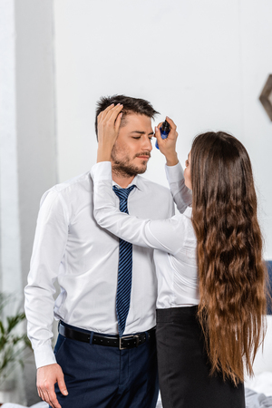girlfriend styling boyfriend hair in morning at home, social role concept