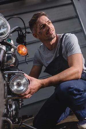 smiling adult mechanic fixing motorcycle headlamp in garage