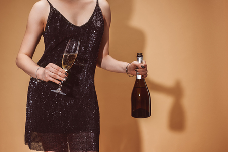 cropped image of woman in party dress holding glass and bottle of champagne on beige