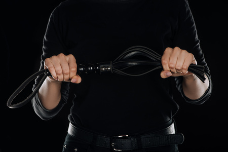 cropped view of female hands tightly holding leather flogging whip isolated on black