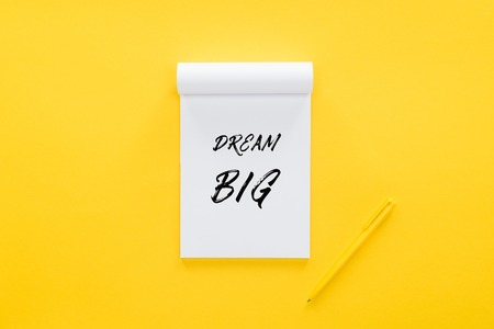top view of notebook with dream big quote on yellow, goal setting concept