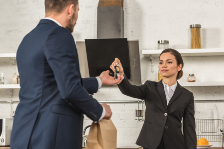 girlfriend giving lunch and car keys to boyfriend in morning at kitchen, sexism concept