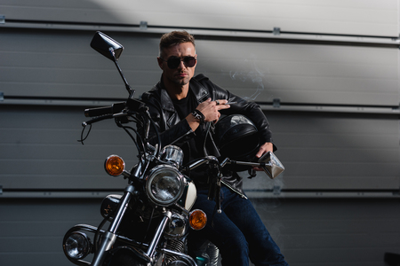 handsome guy in black sunglasses and leather jacket sitting on motorcycle in garage Banco de Imagens