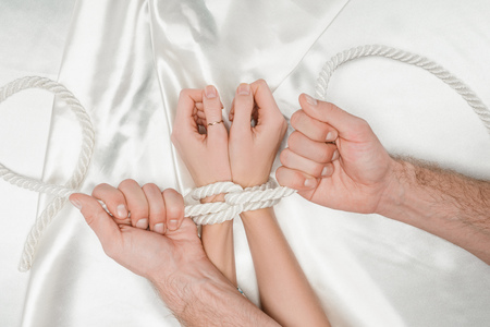 top view of male hands tightly bounding female hands with rope