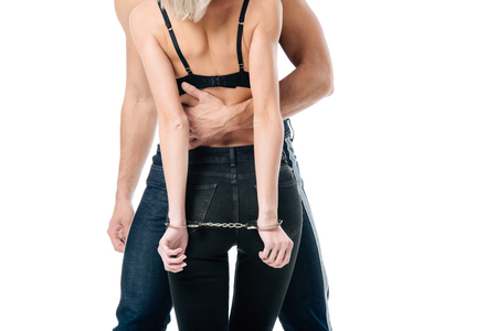 cropped view of man hugging handcuffed woman in bra from behind isolated on white